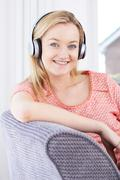 Young Woman Listening To Music On Wireless Headphones - stock photo