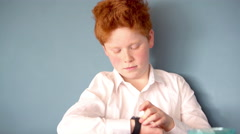 Boy talking into smartwatch - stock footage