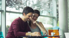 Couple using digital tablet at cafe - stock footage