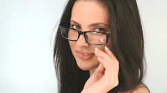 Portrait of a girl with long hair, she poses in glasses on a white background - stock footage