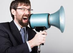 Bearded businessman yelling through bullhorn. Public Relations. man expresses Stock Photos
