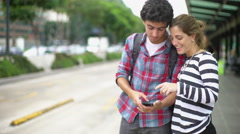 Travelers looking up bus schedule on smartphone while waiting for bus Stock Footage