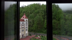 Look out countryside hotel window, green woody slope, road, modern building Stock Footage