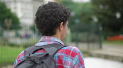 Young man looking over shoulder at camera while walking Stock Footage
