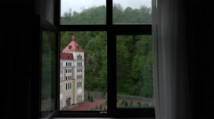 First person view look out hotel window, rural mountain area, green woody slope Stock Footage