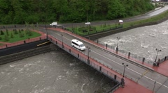 Small white bus drive on road bridge, over small cloudy water, slow down Stock Footage