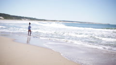 Woman wading in sea, looking at view Stock Footage