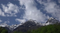 Fluffy white clouds quickly fly and swirl above mountain range, rocky peaks Stock Footage