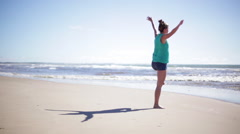 Woman standing in yoga tree pose at the beach Stock Footage