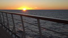 POV, sun on horizon shines through cruise ship deck and railing at sunset Stock Footage
