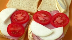 Making sandwich with tomato, ham, cheese, radish, mayonnaise - stock footage