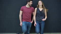 Couple leaning against wall and talking Stock Footage