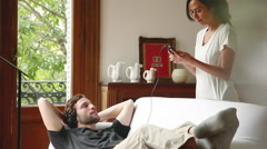 Woman introducing boyfriend to new sounds on mp3 player Stock Footage