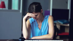 Woman sitting at desk holding head Stock Footage