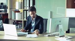 Businessman engrossed in paperwork Stock Footage