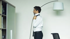Man getting dressed, tying tie - stock footage