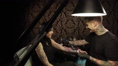 4K UHD video of professional tattoo artist makes a tattoo on a young girl's hand Stock Footage