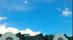 the formation of clouds in the sky on a clear day on a background of green roof - stock footage