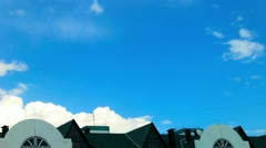 The formation of clouds in the sky on a clear day on a background of green roof Stock Footage