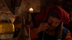 Medieval man eat and drink in ancient castle kitchen interior in 4K UHD video. Stock Footage