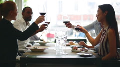 Friends clinking wine glasses in restaurant Stock Footage