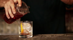 Bartender pouring cocktail into glass Stock Footage