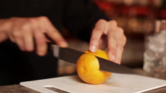 Bartender slicing orange to use in mixed drink Stock Footage