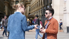 Guys by entrance of Vittorio Emanuele shopping Gallery use smart phones Stock Footage
