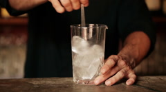 Bartender stirring ice cubes in glass Stock Footage