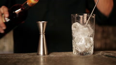 Bartender adding campari to cocktail Stock Footage