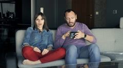 Couple fighting, arguing over money sitting on sofa at home Stock Footage