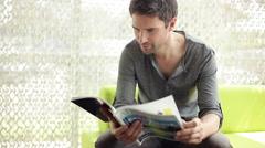 Man reading magazine Stock Footage