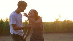 Young couple walking in field and holding hands Stock Footage