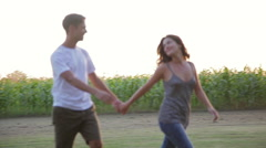 Young couple walking and holding hands in field Stock Footage