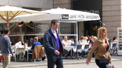 Square Duomo in Milan Italy - people rest in street restaurant eating drinking Stock Footage