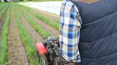 Farmer using rototiller in agricultural field Stock Footage