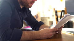 Man pausing to check smartwatch while reading documents - stock footage