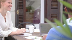 Woman chatting with companion at outdoor cafe Stock Footage