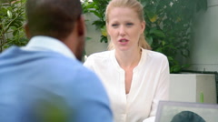 Woman talking with male companion outdoors - stock footage