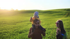 Happy young family with little son on father shoulders laughing in sunset nature Stock Footage