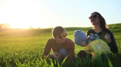 Young parents and little son sit in green grass have fun talk summer countryside Stock Footage