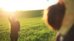 Happy mother wave hand to husband carrying son on shoulders in sun green meadow - stock footage