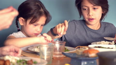 Boy stealing meatball from his little sister's plate during dinner Stock Footage