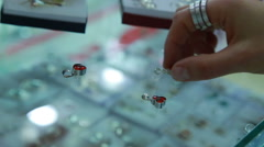 Woman choosing a earrings at the store - stock footage