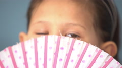 Little girl peeking over top of fan, portrait Stock Footage