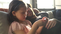Father and daughter looking at smartphone together Stock Footage