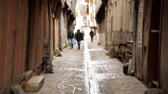 Pedestrians walking in narrow alleyway, Troyes, France Stock Footage