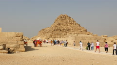 Zoom Out - Tourists Walk Past remains of Smaller Pyramids of Giza - Egypt - stock footage