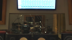 Drummer recording tracks in a studio, viewed from the control room Stock Footage