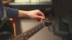 Tuning an electric guitar - stock footage